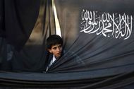 A Palestinian boy looks through the flag of Hizb ut-Tahrir, or Party of Liberation, during a rally in the West Bank city of Ramallah.