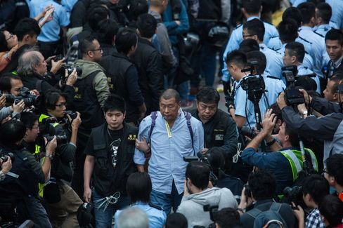 Hong Kong police officers detain Lai during raucous street protests in December.