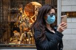 A pedestrian wearing a protective face mask takes a selfie outside a store in Milan on Feb. 25.