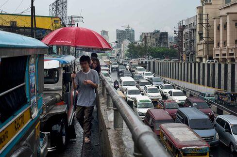 Pedestrians walk past stalled traffic in Manila.