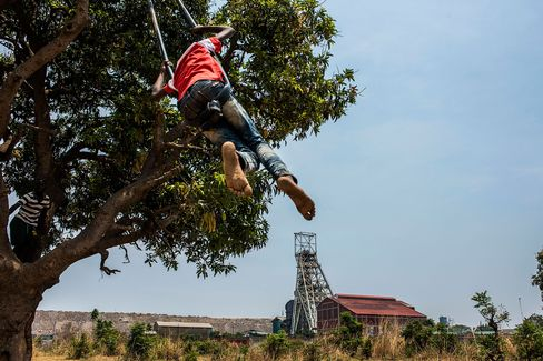 A child swings in a tree near a Glencore Zambian copper mine.