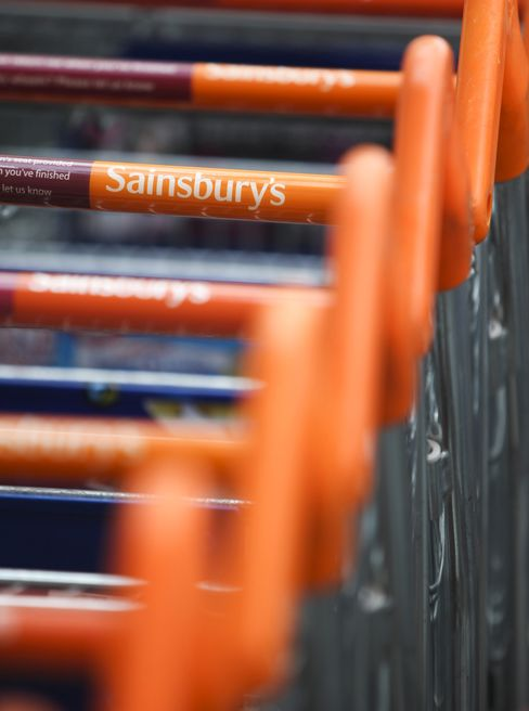 Shopping Carts Sit Outside A Sainsbury's Supermarket