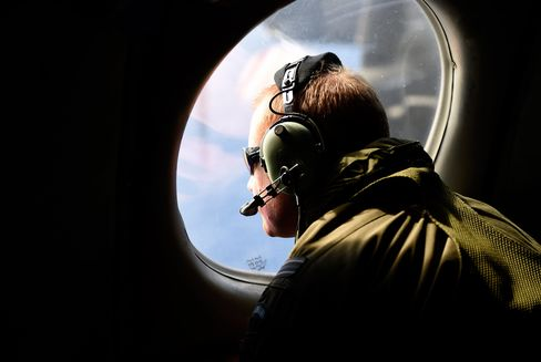 A crew member looks out an observation window aboard a Royal New Zealand Air Force (RNZAF) P3 Orion maratime search aircraft as it flies over the southern Indian Ocean looking for debris from missing Malaysia Airlines flight MH370 on April 11, 2014.