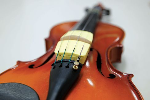 Jamit, a collection of sensors placed on the bridge of a violin that uses Bluetooth to send the player's performance data to a tablet app.