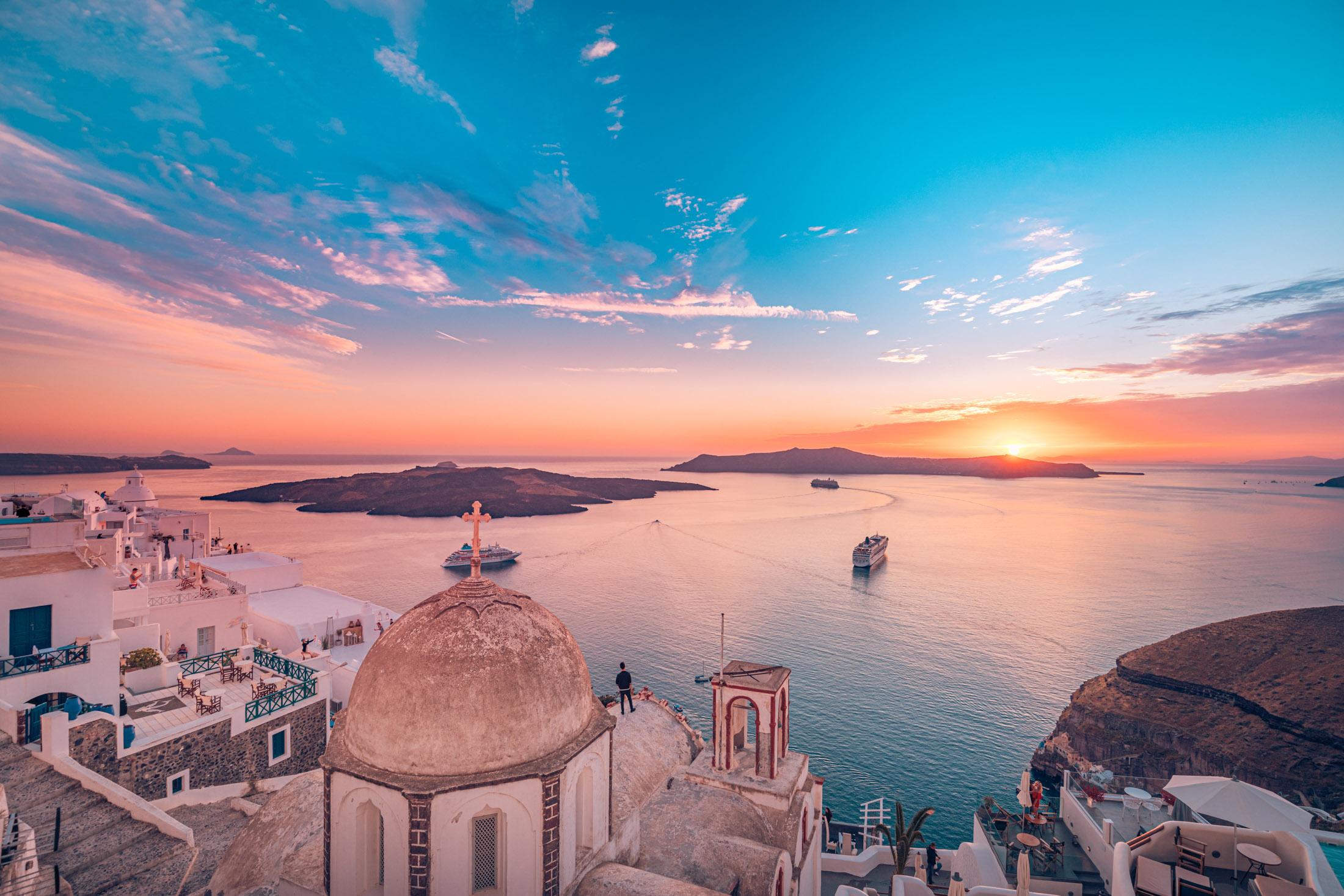 Εκπληκτική βραδινή θέα στα Φηρά, την Καλντέρα, το ηφαίστειο της Σαντορίνης, Ελλάδα με κρουαζιερόπλοια στο ηλιοβασίλεμα.  Δραματικός συννεφιασμένος ουρανός