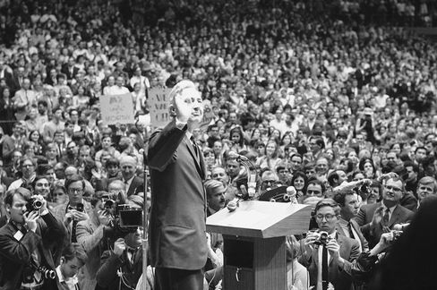 Minnesota Sen. Eugene McCarthy holds his hand up for quiet, as he addressed some 15,000 people on March 26, 1968 at coliseum in Madison.