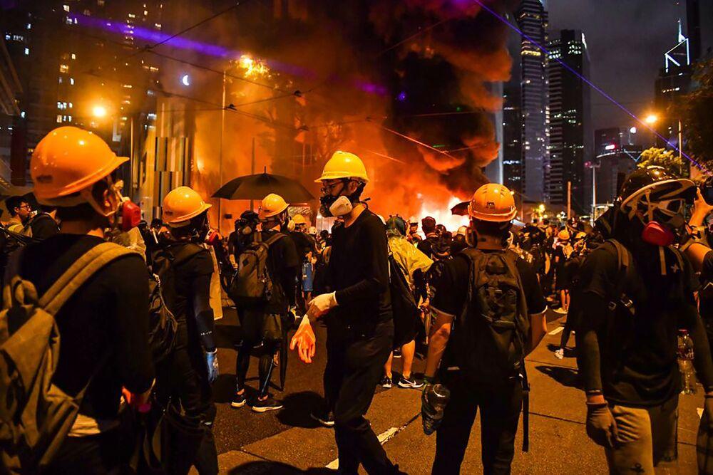 Protestujący stają przed barykadą, którą podpalili 31 sierpnia w dzielnicy Wan Chai w Hongkongu.