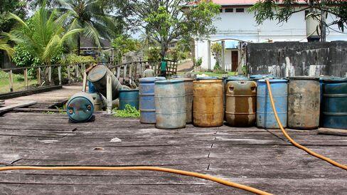 Loading and unloading gasoline barrels on the outskirts of Mabaruma.