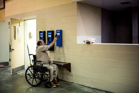 A prisoner at a medium-security prison cleans the cell block's pay phones in Cranston, Rhode Island.