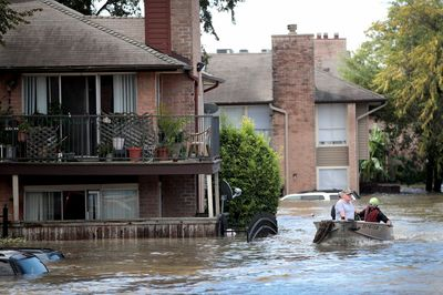 Rescue workers and volunteers help to rescue residents of an apartment complex after it was inundated with water in Houston, on Aug. 30.