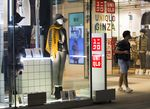 A shopper exits a Uniqlo store, operated by Fast Retailing Co., at night in the Ginza district of Tokyo.
