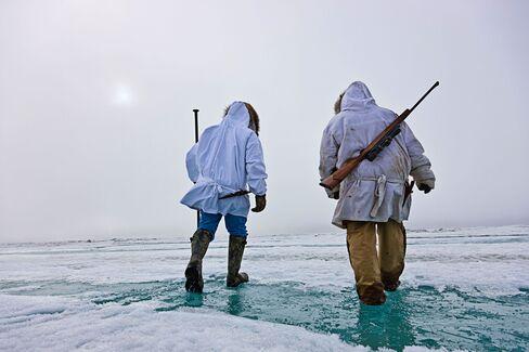Inupiaq Eskimo hunters carry a rifle and walking stick while walking over the shore ice along the Chukchi Sea, Barrow, Alaska.