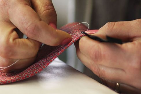 A label is sewn by hand onto a finished tie.