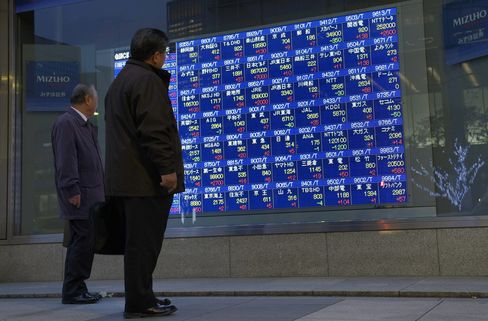 Pedestrians look at an electronic stock board outside a securities firm in Tokyo. Photographer: Akio Kon/Bloomberg