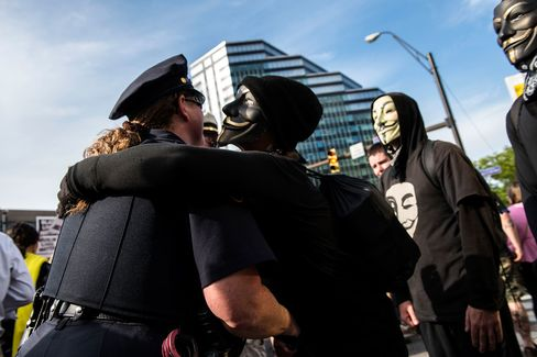 "An ""Anonymous"" protester embraces a police officer in downtown Cleveland on July 17, 2016."