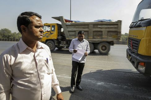 Manoj Zhope, an anti-encroachment officer, right, and Ajit Tandel, sanitary officer from Flying Squad, monitor papers of incoming debris trucks from Mumbai at Vashi in Navi Mumbai, India.