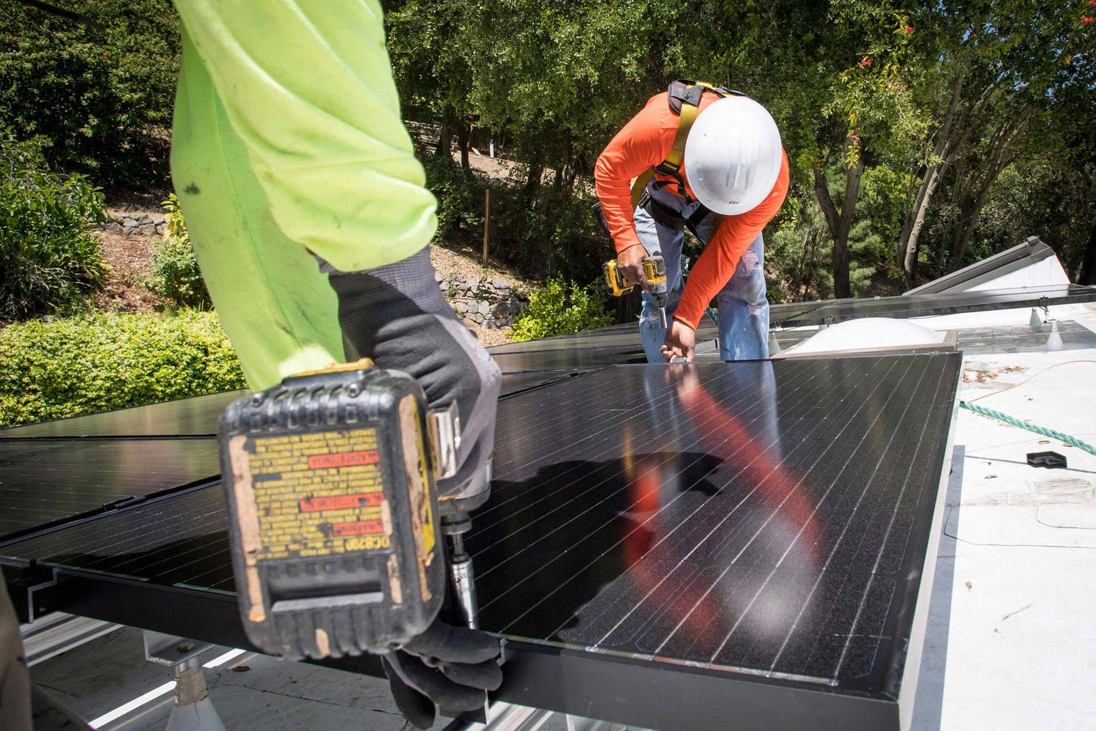 Petersen Dean Inc. employees install solar panels on the roof of a home in Lafayette, Calif., on May 15, 2018.
