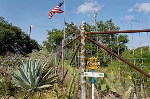 A U.S. flag flies above a Nu Star Logistics petroleum pipeline warning sign by a fence at the entrance to Dr. Michael Vickers' ranch located south of Falfurrias, Texas on July 3