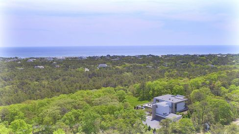 The house is situated on top of a hill, with views of the ocean.