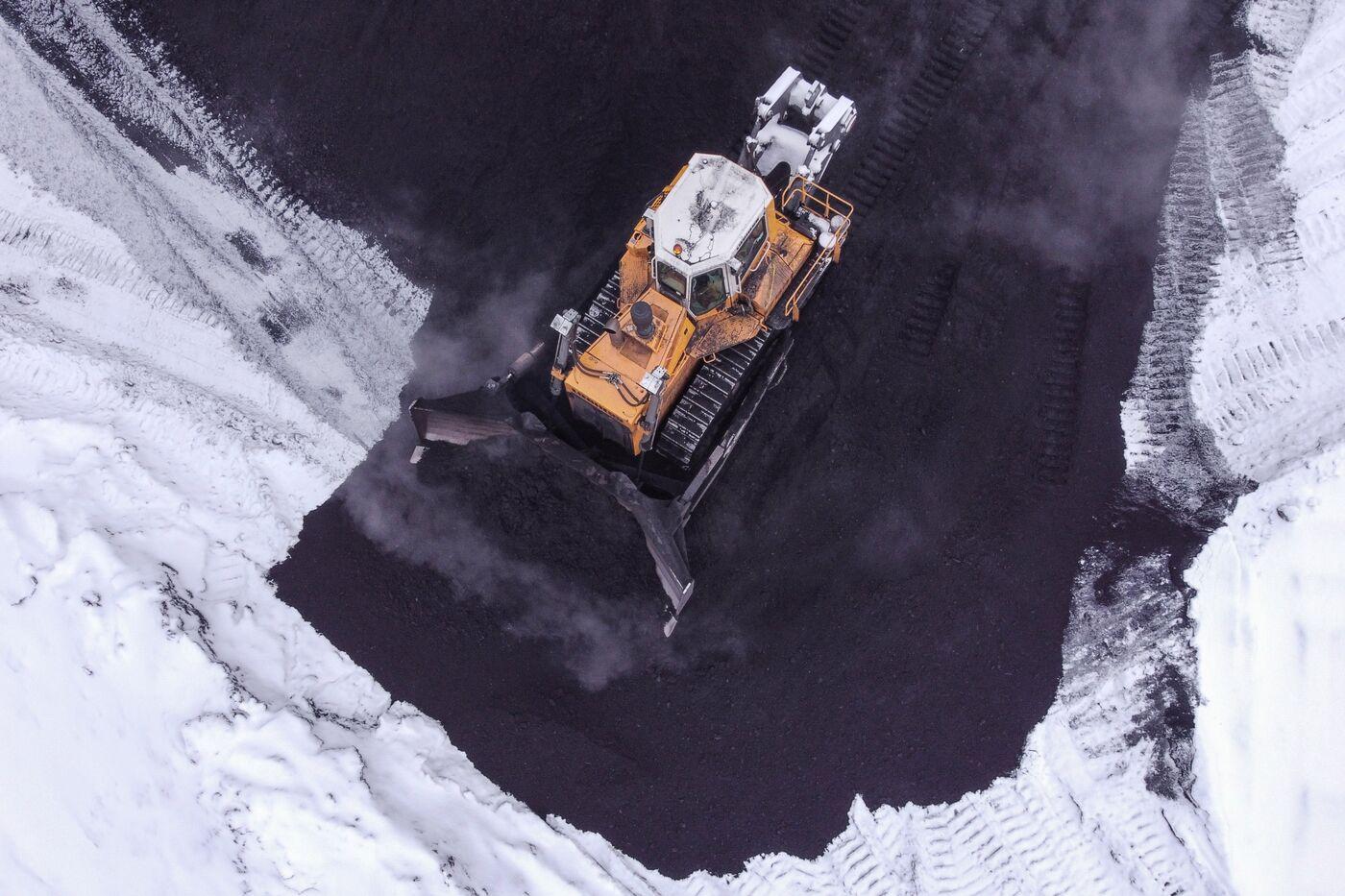 A bulldozer moves piles of coal at the Osinnikovskaya coal mine in Osinniki, Russia.