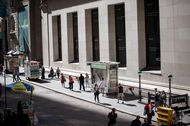 Pedestrians walk along Wall Street near the New York Stock Exchange (NYSE) in New York, U.S., on Friday, Sept. 8, 2017.
