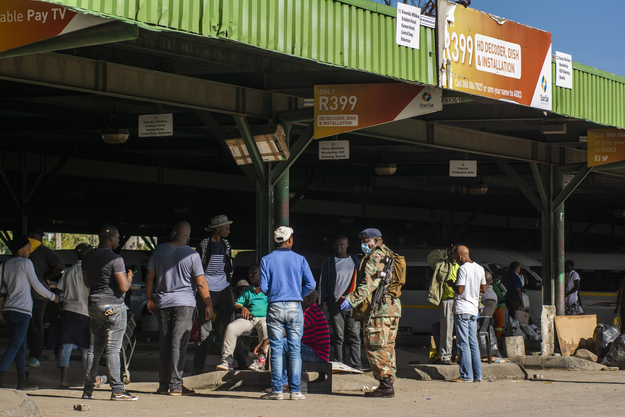 A South African National Defence Force soldier speaks with a group of people at a taxi rank in Rustenburg, South Africa.