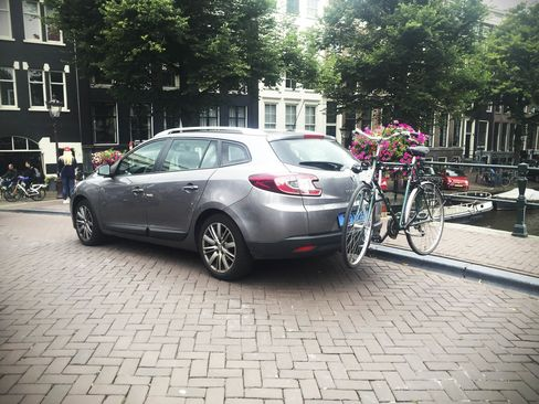 An UberBike car picks up a passenger (and wheels) in Amsterdam's canal zone