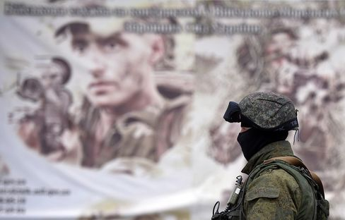 A Soldier Stands in front of a Recruitment Poster