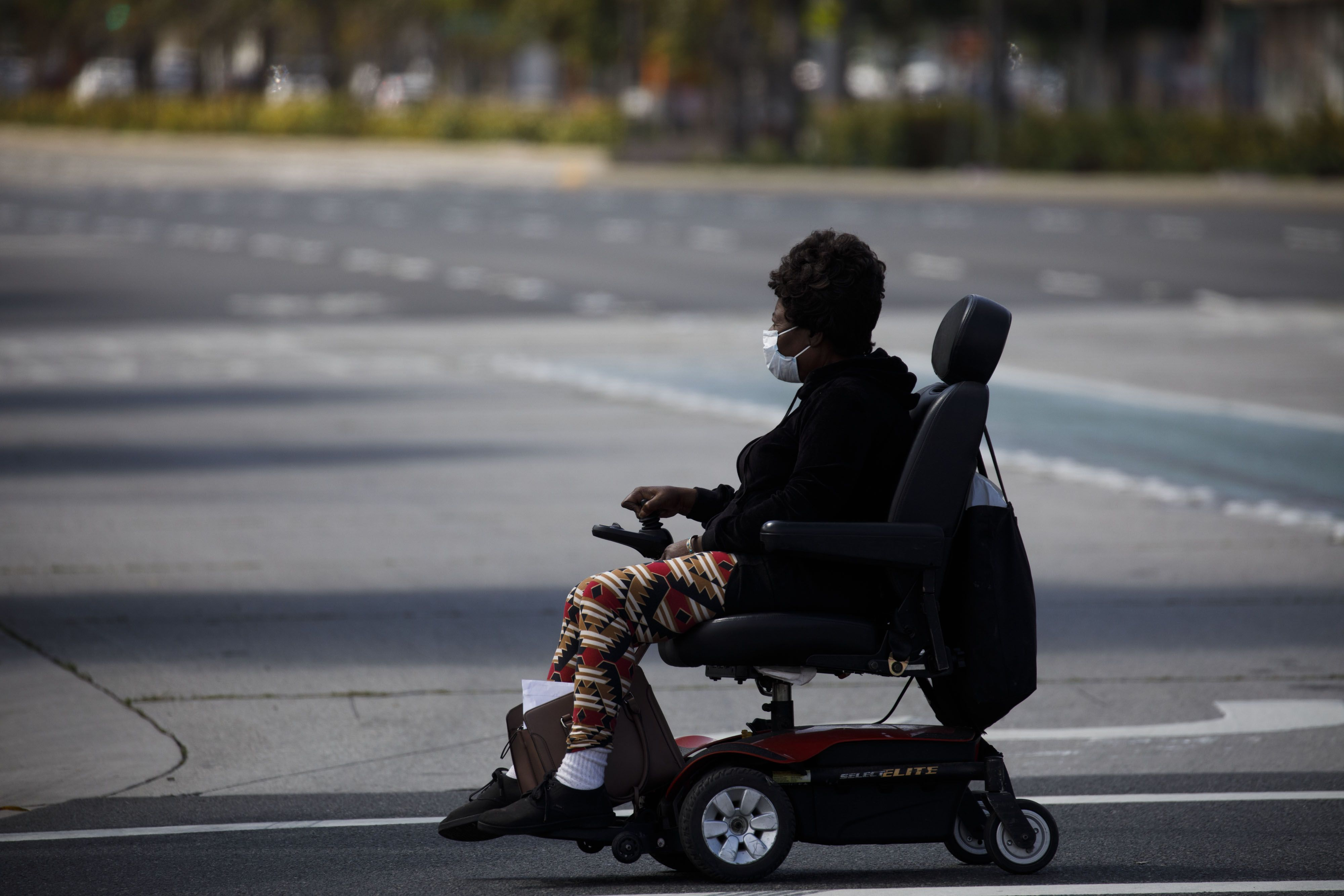 A person in an electric wheelchair crosses a street inHawthorne, California. Adding bike infrastructure is a boon for cyclists, but some street redesigns can make getting around harder fordisabled road users.