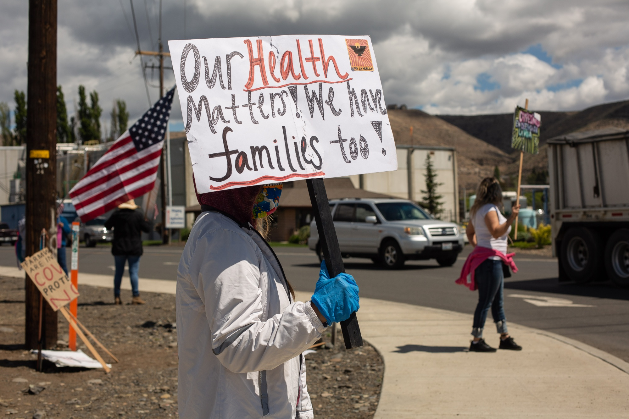 Demonstrators hold signs during a strike outside of a Allan Brothers Fruit apple packing house in Naches, Washington, on May 18, 2020.