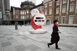 A pedestrian wearing a protective face mask walks past the countdown clock for the Tokyo 2020 Olympic Games.