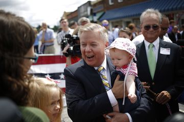 Republican Senator Lindsey Graham holds the baby of a supporter after announcing the launch of his campaign to seek the 2016 Republican Presidential nomination in Central, South Carolina, U.S. on Monday, June 1, 2015. Photographer : Luke Sharrett / Bloomberg