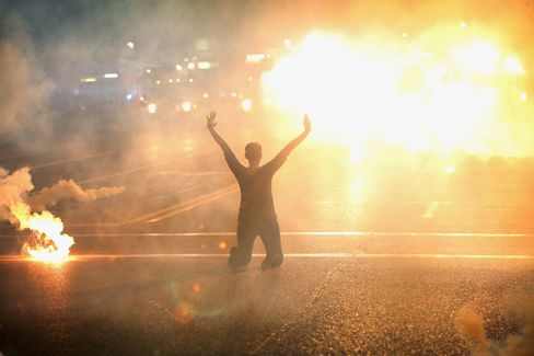 Tear gas reigns down on a woman kneeling in the street with her hands in the air after a demonstration over the killing of teenager Michael Brown by a police officer in Ferguson. Photographer: Scott Olson/Getty Images