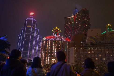 Pedestrians walk in front of the Bank of China building (left) and the Casino Grand Lisboa in Macau on March 12, 2015.