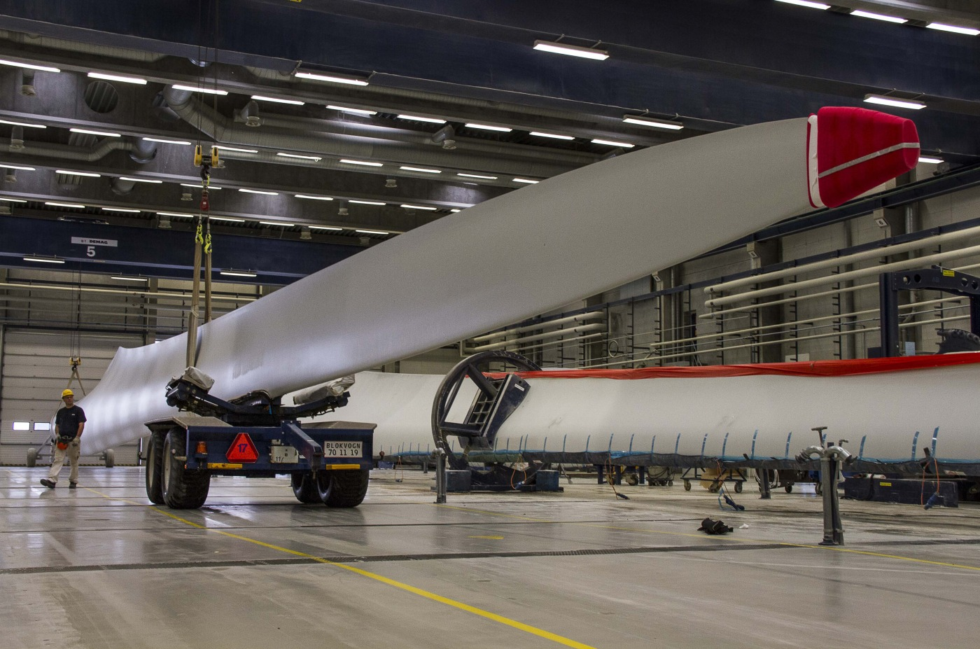 An employee walks between wind turbine blades at the Vestas Wind Systems A/S blade factory in Lem, Denmark.