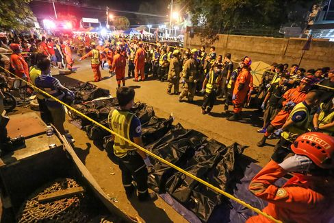 Rescue workers gather bags containing the bodies of victims at a night market in Davao City on Sept. 3.