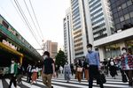 Pedestrians wearing protective masks cross a street in the Yurakucho district of Tokyo, Japan.
