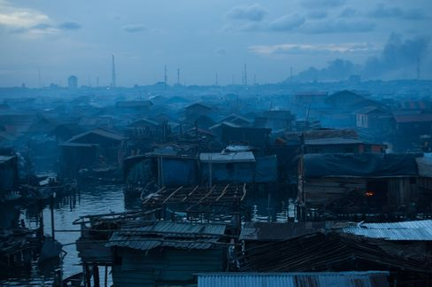 A slum stands at nightfall in Lagos, Nigeria. With 1.5 million people a week migrating to cities -- mostly in the developing world -- the new battlefields will be slum-ridden yet wired megalopolises such as Lagos and Mumbai, where insurgents and crime bosses can control lawless rings of territory. Photographer: Mohammed Elshamy/Anadolu Agency via Getty Images