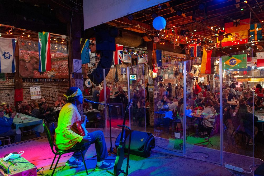 A musician performs behind plexiglass inside a venue at the Juke Joint Festival in Clarksdale, Mississippi.