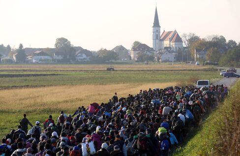 Migrants are escorted near Rigonce