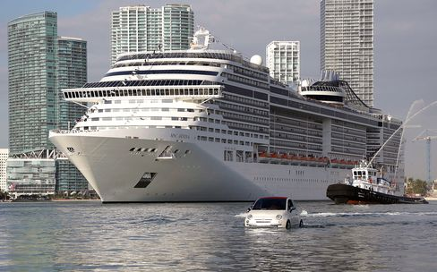 The MSC Divina cruise ship arrives at the Port of Miami escorted by a Fiat 500 watercraft, on Nov. 19, 2013.