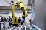 A Fanuc Inc. robotic arm operates to inspect a gear with the AI system, developed by Musashi Seimitsu Industry Co. and Abeja Inc., at the AI Expo - Artificial Intelligence Exhibition & Conference in Tokyo, Japan, on Wednesday, April 4, 2018.