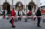 TOPSHOT - People wait in line at a safety distance to shop at the food market of Porta Palazzo in Turin on May 4, 2020.