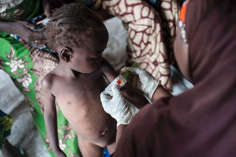A woman measures the diameter of a girl's arm suffering from severe acute malnutrition near Maiduguri.
