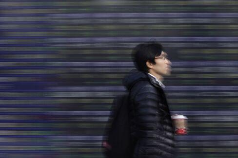 株価ボード前の歩行者