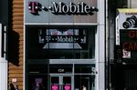 Pedestrians pass in front of a T-Mobile US Inc. store in New York.