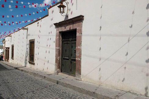 Outside, a nondescript stucco wall.