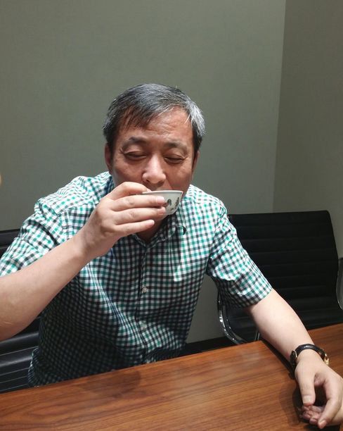 """Billionaire art collector Liu Yiqian holds the 15th century Ming dynasty ceramic nicknamed the """"Chicken Cup,"""" which was bought for $36 million at a Hong Kong auction."""