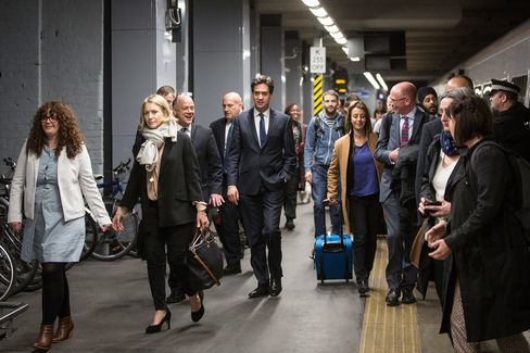 Labour Leader Ed Miliband with members of his media team and their security detail arrive at King's Cross railway station in London, on April 23, 2015.