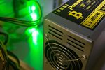 A bitcoin logo sits on a LL 1800W power unit supplying cryptocurrency mining machines at the SberBit mining 'hotel.'